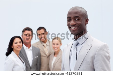 Smiling attractive Afro-American businessman standing in front of his team