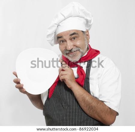 smiling attractive chef holding   white plate