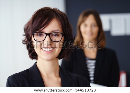 Smiling attractive manageress or team leader posing in the foreground with a team member or co-worker visible in the background as a blur, head and shoulders portrait
