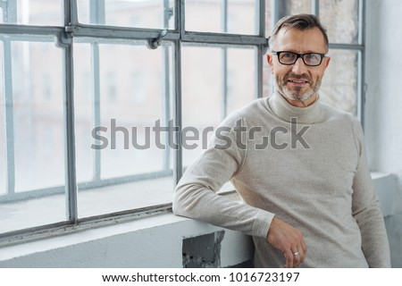 Smiling attractive mature man wearing glasses leaning on the sill of a large bright window with copy space looking at the camera