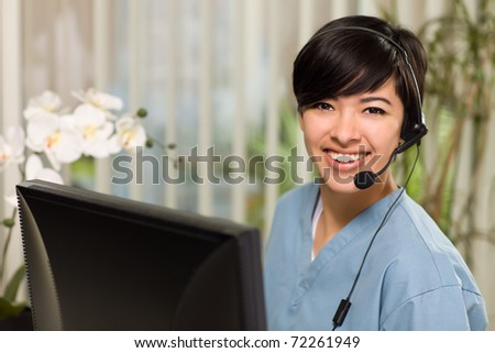 Smiling Attractive Multi-ethnic Young Woman Wearing Headset and Scrubs Near Her Computer Monitor.