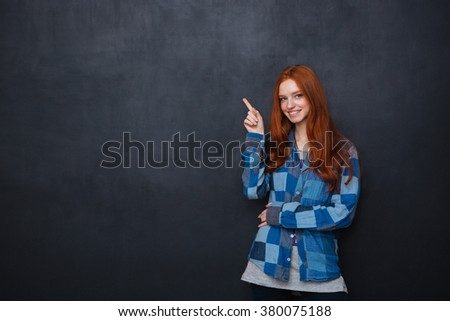 Smiling attractive redhead young woman in checkered shirt pointing on copyspace over chalkboard background