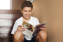 Smiling attractive teen boy sitting at home on steps and reading magazine. Cheerful guy in white t-shirt is sitting at home, reading comic book. Schoolboy is reading paper book while resting home.