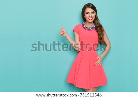 Smiling attractive woman in pink mini dress is posing with hand on hip and showing thumb up. Three quarter length studio shot on turquoise background. #731512546