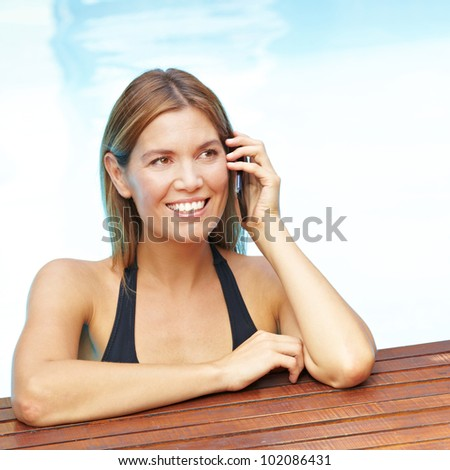 Smiling attractive woman using cell phone in swimming pool