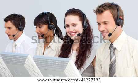 Smiling attractive woman working with her team in a call center