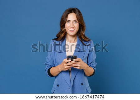 Smiling attractive young brunette woman 20s wearing basic jacket standing using mobile cell phone typing sms message looking camera isolated on bright blue colour wall background, studio portrait