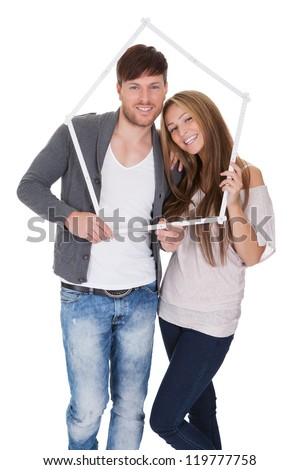 Smiling attractive young couple posing standing close together on a white background