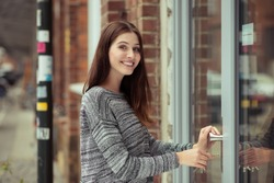 Smiling attractive young female student entering a commercial building looking at the camera as she pushes open the glass door