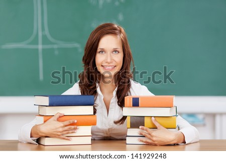 Smiling attractive young female student with her textbooks sitting at a desk in the classroom in front of the blackboard