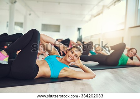 Smiling attractive young woman doing aerobics in the gym with a group of young women in a health and fitness concept