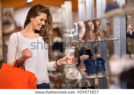 Smiling attractive young women shopping at shoes store