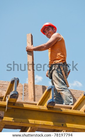 Smiling authentic construction worker with beam standing on top of formwork