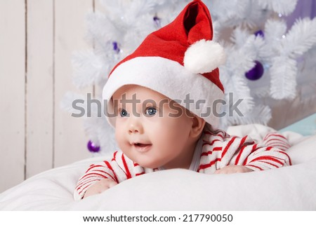 Smiling baby boy in Santa`s hat on the soft white pillow under the decorated Christmas tree