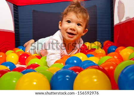 Smiling baby boy lying in colorful balls inside a playpen