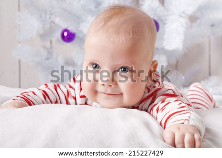 Smiling baby boy on the soft white pillow under the decorated Christmas tree