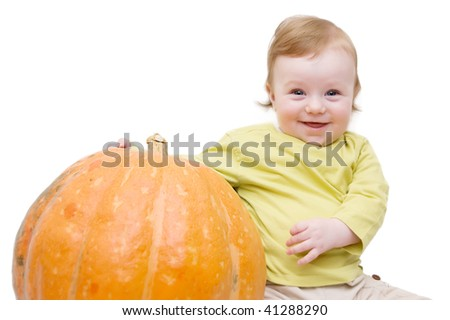Smiling baby boy playing with pumpkin over white