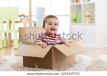 Smiling baby boy sitting inside cardboard box after moving to a new apartment