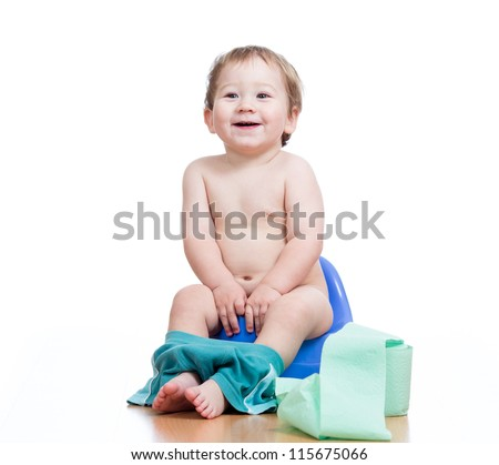 smiling baby boy sitting on chamber pot with toilet paper roll