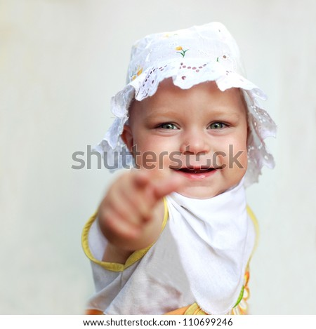 Smiling baby girl pointing a finger, on white background. Focused on her face.