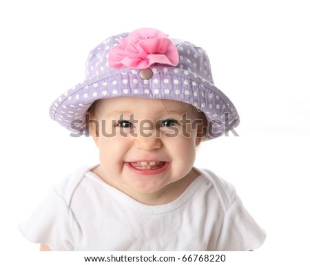 Smiling baby girl showing teeth wearing a purple polka dot hat with pink flower isolated on white background