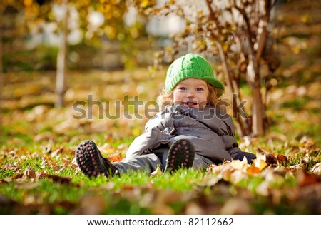 Smiling baby girl sitting on yellow leaves in autumn park