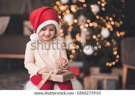Smiling baby girl wearing santa claus hat and pajamas open xmas present box over Chrismas tree with glowing lights close up. Childhood. Winter holiday season.
