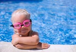 Smiling baby girl  wearing swimming glasses in swimming pool