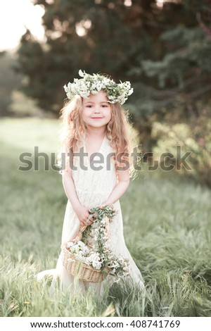 Smiling baby girl 3-4 year old holding basket with flowers outdoors. Wearing floral wreath. Looking at camera. Childhood. Elegance.