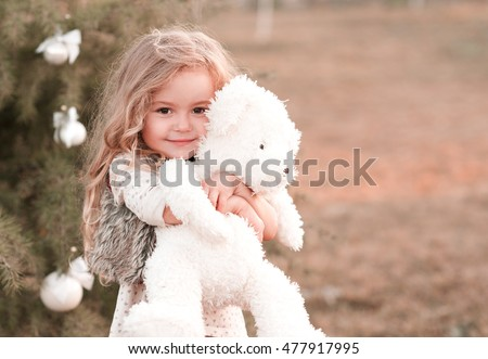 Smiling baby girl 4-5 year old holding teddy bear outdoors. Looking at camera. Childhood. Playful. Wearing stylish clothes.