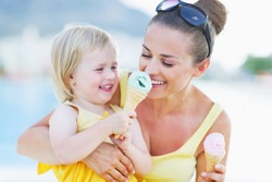 Smiling baby giving mother ice cream