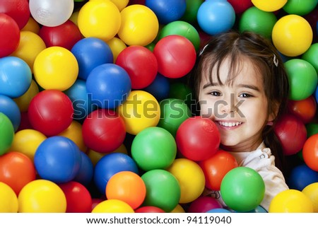smiling baby in balls sea