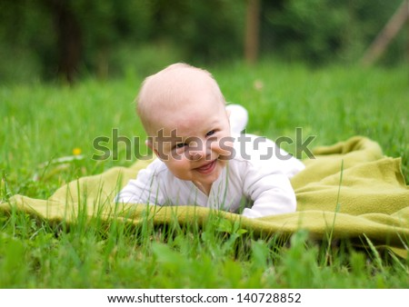 Smiling baby lying in a park