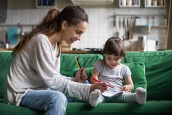 Smiling baby sitter and preschool kid girl drawing with colored pencils sitting on sofa together, single mother and child daughter playing having fun, creative family activities at home concept
