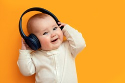 Smiling baby with headphones listening to music on the orange background. Technology for kids