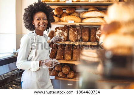 Smiling baker woman standing with fresh bread at bakery. Happy african woman standing in her bake shop and looking at camera. Satisfied baker with breads in background. Smiling woman at bakery shop