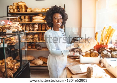 Smiling baker woman standing with fresh bread at bakery. Happy african woman standing in her bake shop and looking at camera. Satisfied baker with breads in background. Beautiful  woman at bakery shop