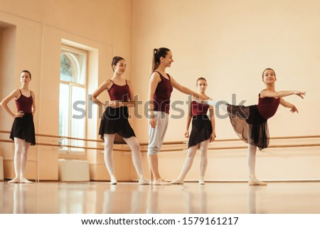 Smiling ballerina dancing while ballet teacher is helping her to improve her posture during rehearsal at dance studio.
