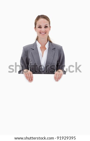 Smiling bank employee holding blank sign in her hands against a white background