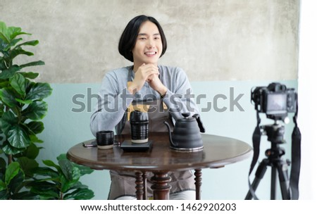 Smiling barista asian man in apron with recording video camera filming and talking on video shooting with how to drip coffee.Startup Small Business Owner Concept. Making blogger or vlogger concept.