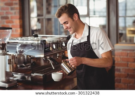 Smiling barista pouring milk into cup at coffee shop