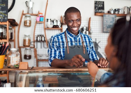 Smiling barista standing behind a counter in a cafe taking a credit card from a customer to pay for her purchase #680606251