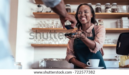 Smiling barista using nfs technology to help a customer pay for a purchase with their bank card in a cafe  #722577382