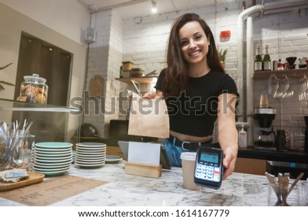 smiling barista woman standing behind the bar with hot coffee drink in paper cup and lunch paper bag for take away holding payment terminal