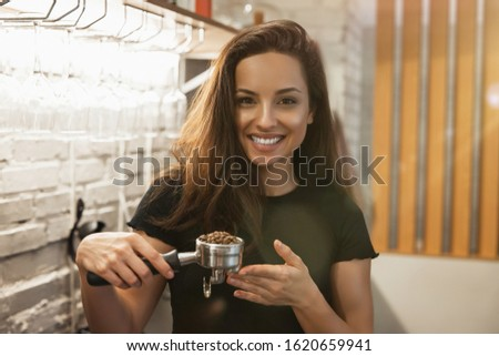 smiling barista woman standing with coffee holder full of ground coffee in her hands , barist work routine.