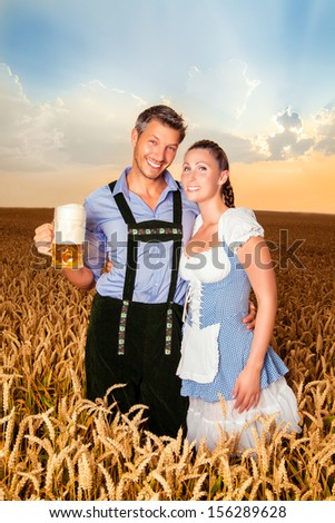 smiling bavarian sunset couple with beer