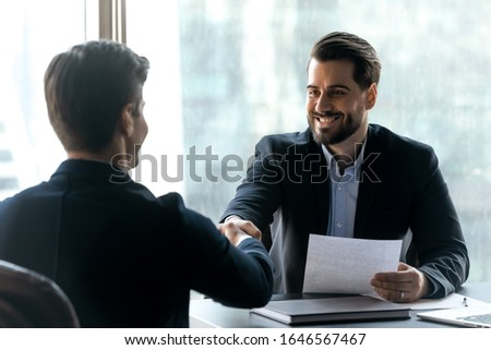 Smiling bearded businessman in suit shaking hands with job seeker. Happy successful male manager making deal with partner. Professional employee holding cv and greeting applicant.