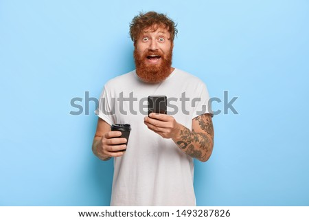 Smiling bearded emotional man has red hair, holds mobile phone, shares great news with friend, gazes at camera with broad smile and bugged eyes, wears casual white t shirt, holds takeaway coffee