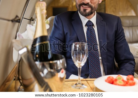 Smiling bearded male sitting in airplane seat at tray table with champagne and strawberry. Focus on man #1023280105