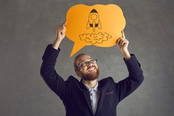 Smiling bearded man in suit holding paper thought bubble with spaceship doodle. Happy businessman in glasses looking at space rocket picture on speech balloon. Business, innovation, success concept